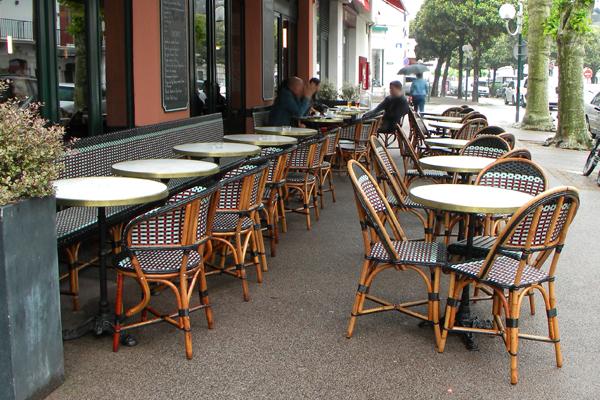 Bar basque et sa jolie terrasse de rue au mobilier en rotin naturel Terrasse de bar au coeur de St Jean De Luz